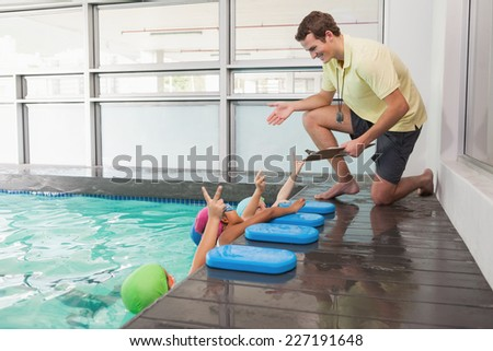Cute swimming class listening to coach at the leisure center - stock photo