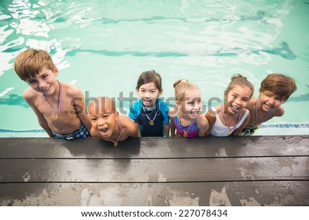 Cute swimming class smiling with medals at the leisure center