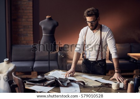 Cute tailor male with beard and glasses in white shirt with brown leather suspenders working near wooden table with threads, apron and scissors in amazing atelier with antique furniture