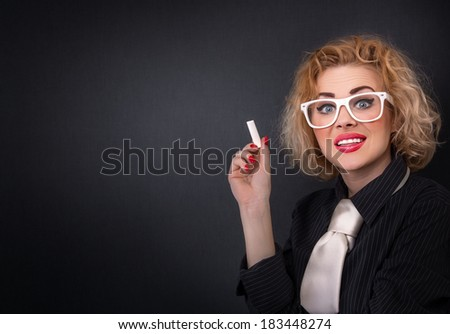 Cute teacher with chalk in front of blackboard, close-up of young professor wit copyspace - stock photo