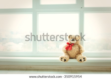 Cute teddy bear at home in white room is sitting near window. Alone bear waiting for a baby boy or girl. - stock photo