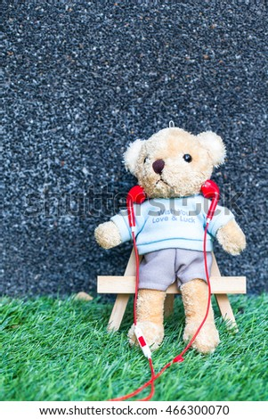 Cute teddy bear listening music from smartphone in garden.