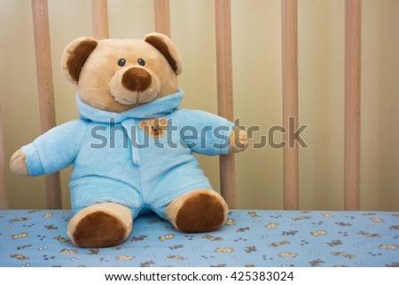 Cute Teddy Bear Stuffed Animal in a Baby Crib - stock photo