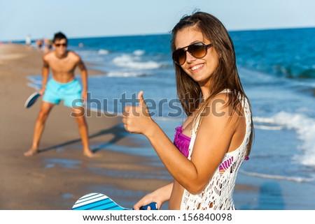 Cute teen beach tennis player doing thumbs up. - stock photo