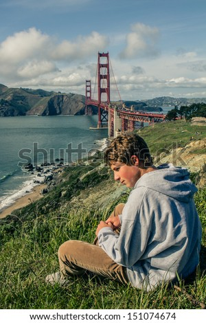 Cute Teen Boy in San Francisco with Golden Gate Bridge in the Background - stock photo