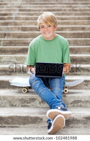 cute teen boy with laptop outdoors - stock photo