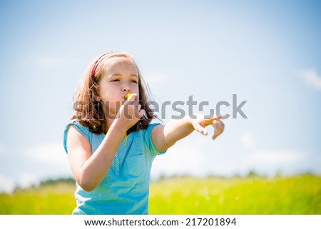 Cute teen girl blowing in whistle and pointing with hand - outdoor in nature - stock photo