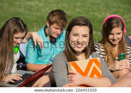 Cute teen girl holding binder with friends - stock photo