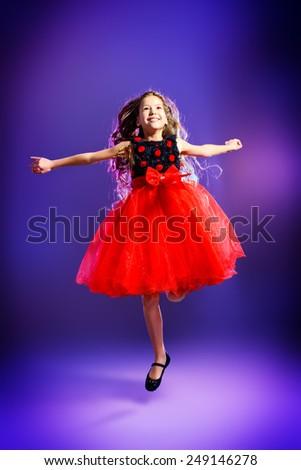 Cute teen girl in a beautiful festive dress dancing at studio. Beauty, children's fashion. Studio shot. - stock photo
