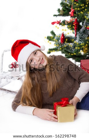 Cute teen girl in Santa hat with gifts under Christmas tree - stock photo