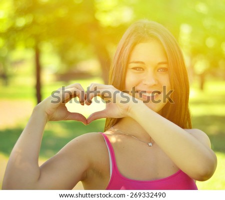 Cute teen girl making heart shape with her hands outdoors - stock photo