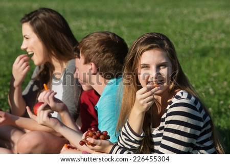 Cute teen girl with friends eating healthy food - stock photo