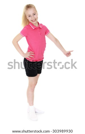 Cute teen girl 12 years a tail on the head in a pink t-shirt and short black shorts stands sideways to the camera. Girl hand shows the sign of all good or OK-Isolated on white background - stock photo