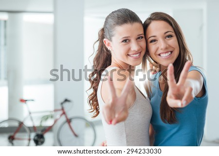 Cute teen girls smiling at camera and making a V sign, adolescence and friendship concept - stock photo