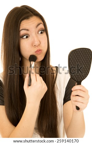 Cute teen model applying makeup making face - stock photo