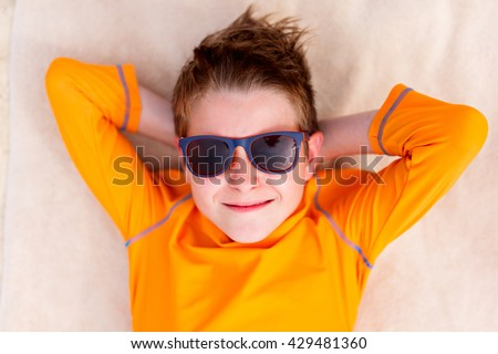 Cute teenage boy lying on a beach towel during summer vacation