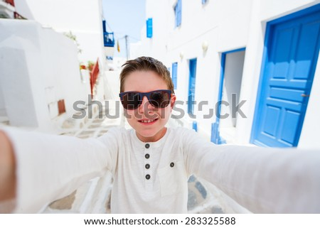 Cute teenage boy making selfie with mobile phone on a street of traditional greek village - stock photo