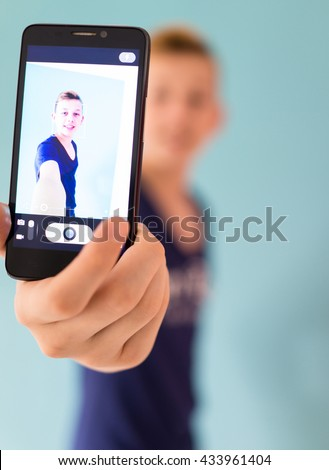 Cute teenage boy taking selfie - stock photo