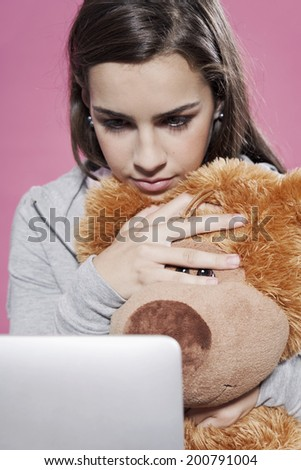 Cute teenage girl embracing soft toy using laptop - stock photo