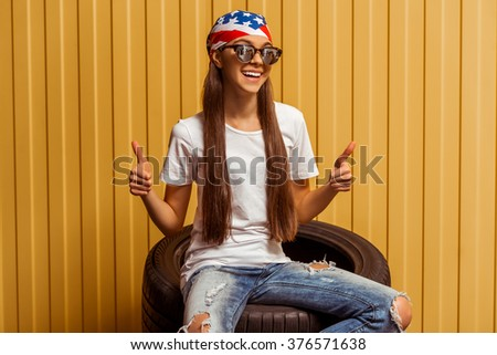 Cute teenage girl in a bandana and sunglasses showing OK sign, looking in camera and smiling while sitting on tires against orange background - stock photo