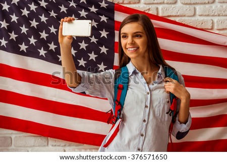 Cute teenage girl in a casual shirt standing with a school backpack against American flag background,making a photo and smiling