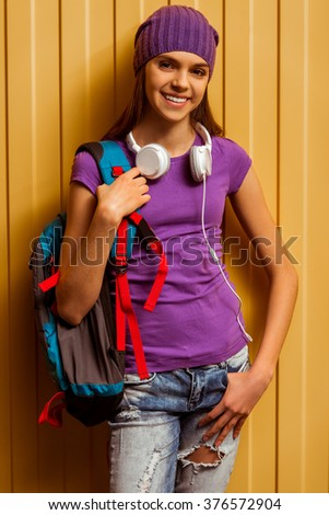 Cute teenage girl in a t-shirt and a cap standing with a school backpack and headphones on an orange background,  looking in camera and smiling - stock photo