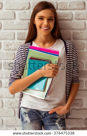 Cute teenage girl in casual clothes holding books, looking in camera and smiling, standing against white brick wall