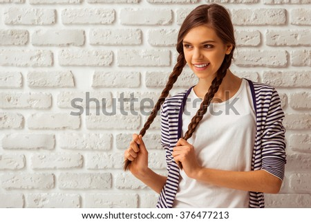Cute teenage girl in casual clothes playing with her braids, looking away and smiling, standing against white brick wall