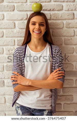 Cute teenage girl in casual clothes standing with an apple on her head against white brick wall, looking in camera and smiling