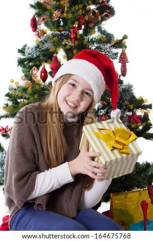 Cute teenage girl in Santa hat with present under Christmas tree - stock photo