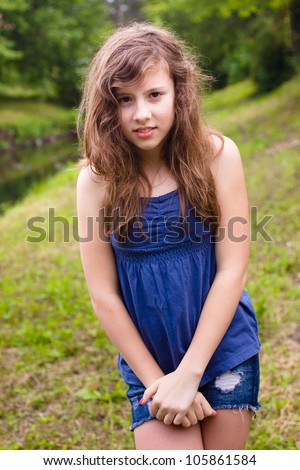 Cute teenage girl looking shy in natural outdoor setting - stock photo