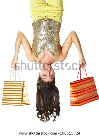 Cute teenage girl posing upside down being happy with shopping - stock photo