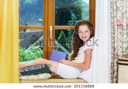 Cute teenage girl siiting on window siil  and reading book