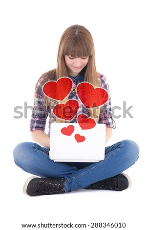 cute teenage girl sitting and sending love messages with laptop isolated on white background - stock photo
