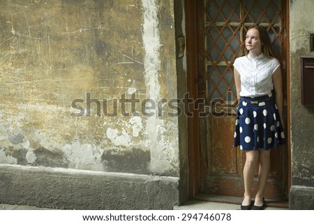 Cute teenage girl stands near the door of the old house. - stock photo