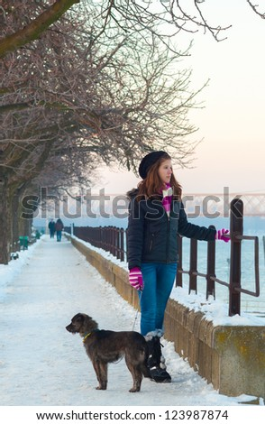 Cute teenage girl walking the dog on cold winter day. - stock photo