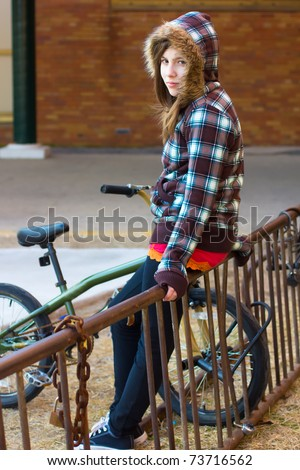 Cute teenage girl with a hood hanging out by the bike rack in the schoolyard - stock photo