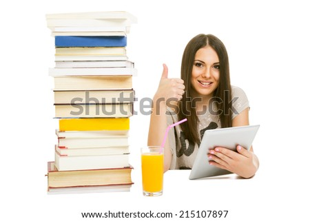 Cute teenage girl with digital tablet and pile of books gesturing thumbs up smiling looking at camera isolated on white background.
