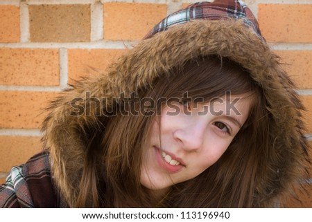 Cute teenage girl with fur lined hood in golden sunlight - stock photo