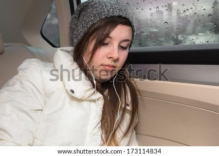 Cute teenage girl with hat and earbuds in backseat of car - stock photo