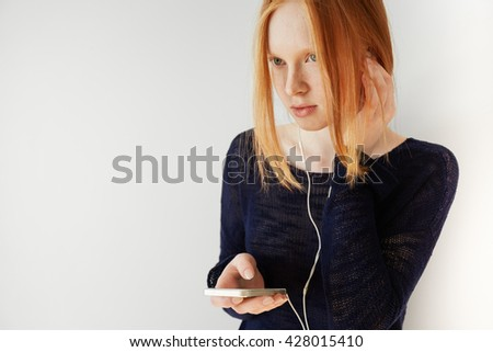 Cute teenage girl with red hair wearing trendy black top, holding smart phone, listening attentively to audiobook on her electronic device. Portrait of young Caucasian woman wearing earphones   - stock photo