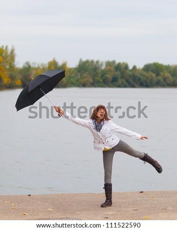 Cute teenage girl with umbrella enjoying cloudy autumn day. - stock photo