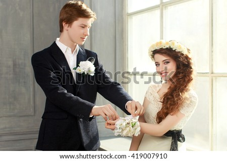 Cute Teenage Prom Couple in beautiful interior - boy giving his date a white floral wrist corsage  - stock photo