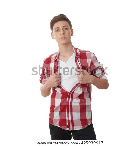 Cute teenager boy acting like a super hero and tearing his red checkered shirt off over white isolated background, half body