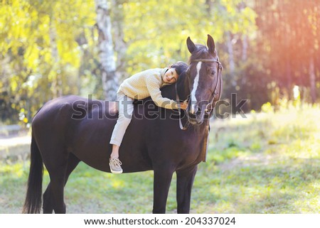 Cute teenager boy and horse in the forest - stock photo