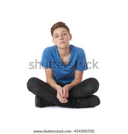Cute teenager boy in blue T-shirt and lotus posture over white isolated background - stock photo