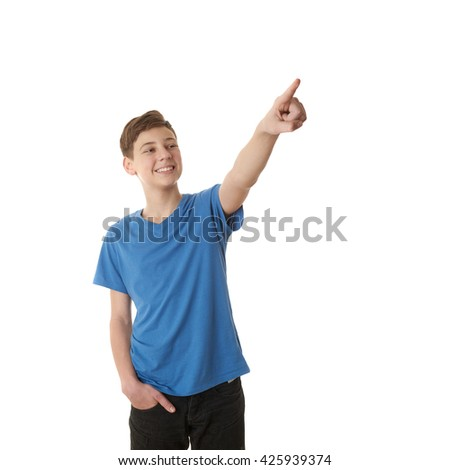Cute teenager boy in blue T-shirt pointing up side over white isolated background, half body - stock photo