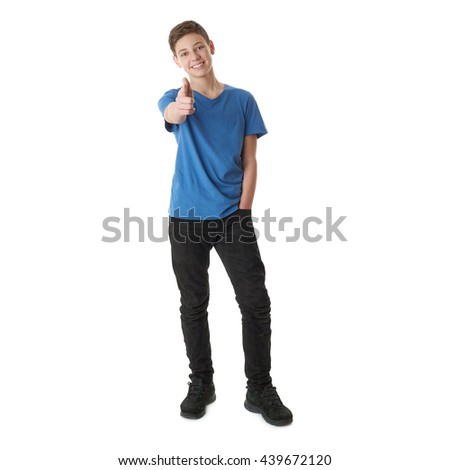 Cute teenager boy in blue T-shirt standing and poinitng forward over white isolated background full body