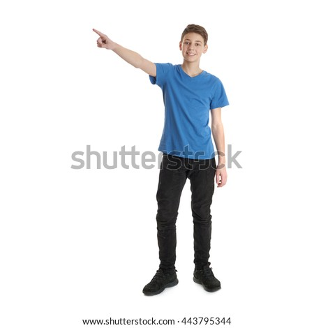 Cute teenager boy in blue T-shirt standing and pointing up side over white isolated background full body