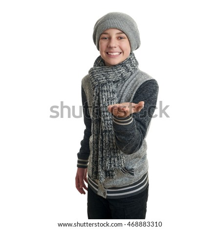 Cute teenager boy in gray sweater, hat and scarf holding something over white isolated background, half body